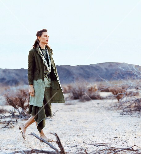 Pensive woman wearing batik coat and skirt walking in desert