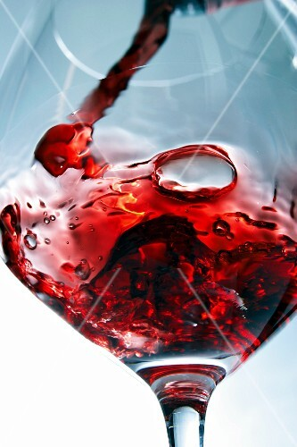 A glass of red wine being swirled
