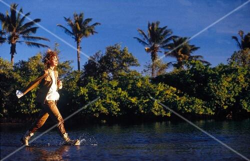 Fashionable woman in safari look wearing suit walking in shallow water