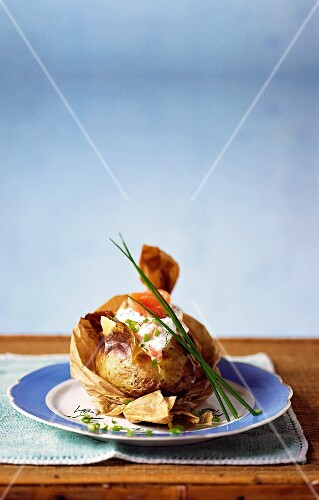 A baked potato in baking paper with smoked salmon and creme fraiche
