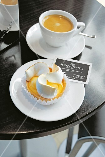 Lemon tart with meringue and coffee in a coffee shop