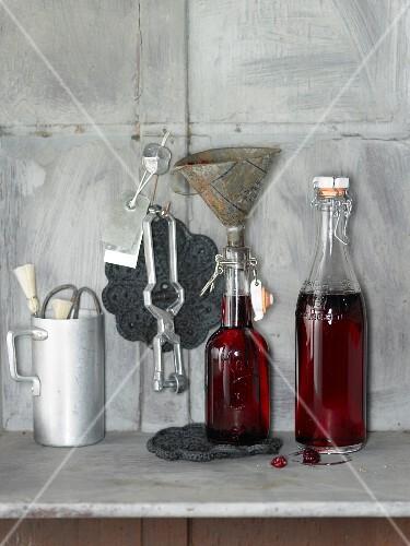 An arrangement of cherry-vanilla syrup in bottles and kitchen utensils