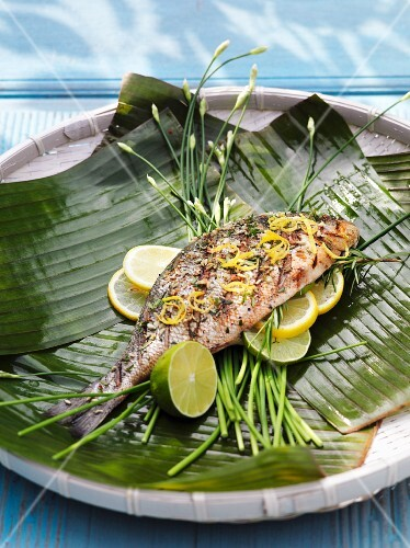 Grilled seabream on banana leaves with lemon slices and lime wedges