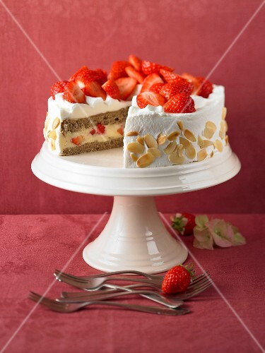 Strawberry cake with flaked almonds on a cake stand