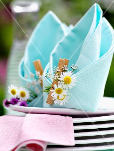Napkins folded like bishop's mitres decorated with daisies and clothes pegs