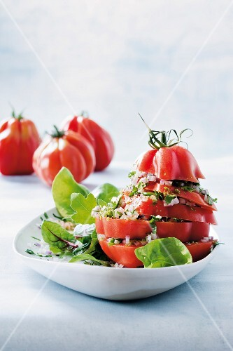 A stack of tomatoes with a coriander and parsley vinaigrette