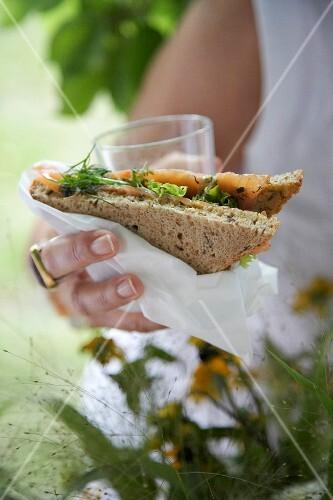 A woman handing a smoked salmon sandwich