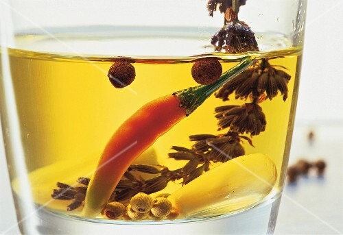 Spices, a chilli pepper and a sprig of lavender preserved in oil (close-up)
