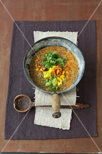 Spicy lentil soup with crispy fired shrimps and mango