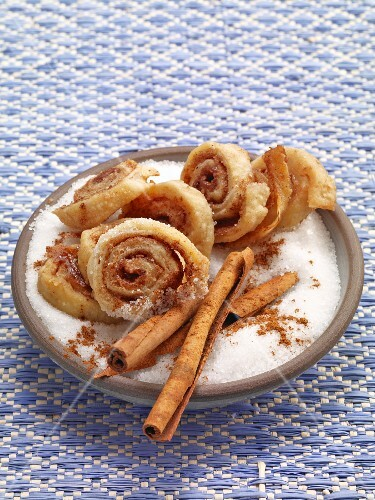 Caramel pastries in a bowl with cinnamon sticks and sugar