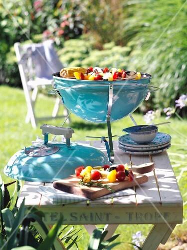 A portable barbecue on a wooden table in a summer garden