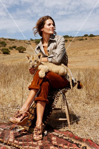 Pretty woman sitting on stool in steppe with a lion cub on her lap, Africa