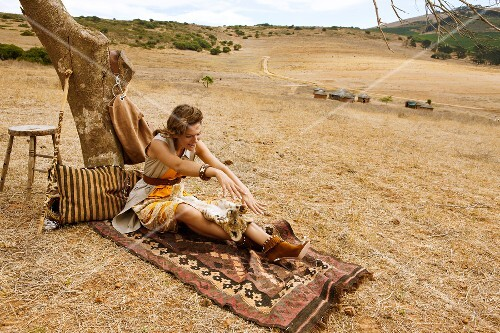 Happy woman sitting on steppe and playing with lion cub, laughing
