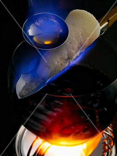 Feuerzangenbowle: rum being poured over a burning sugar cone