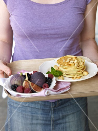 A woman holding a tray of pancakes and a fruit platter
