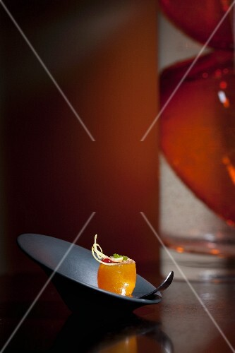 A garnished kumquat served on a spoon (restaurant Alinea, Chicago, USA)