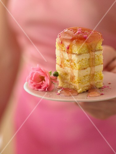 A woman holding a plate of rose petit fours