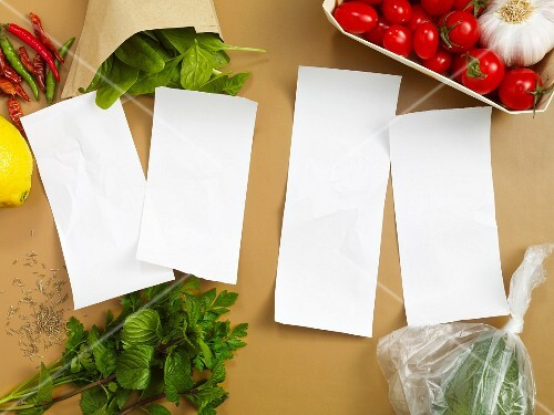 Four blank pieces of paper surrounded by vegetables and herbs