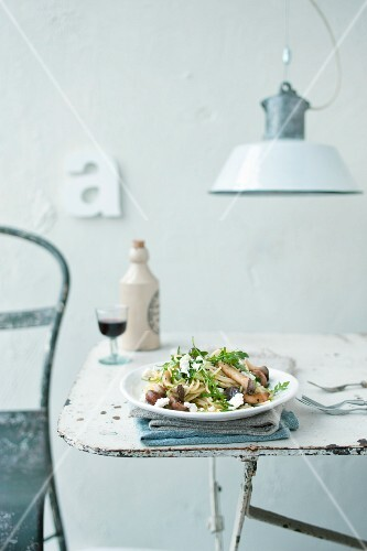 Spaghetti with fried mushrooms on a shabby chic-style table