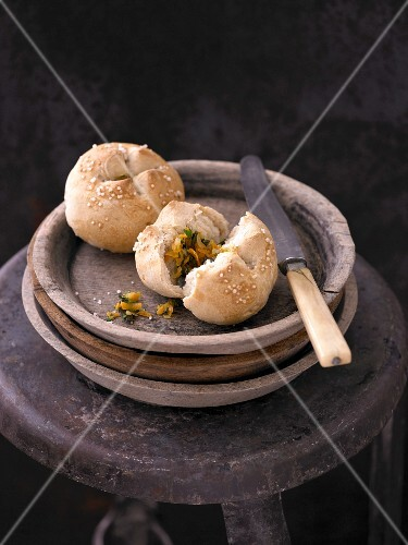 Rye bread rolls with a vegetable filling on a stack of wooden plates