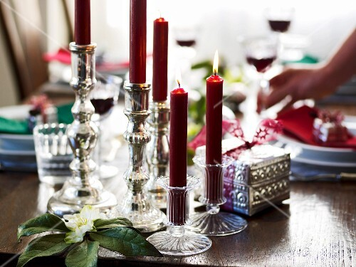 Red candles in various candle holders as Christmas table decoration