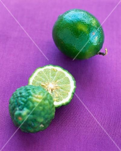 A lime and a kaffir lime on a purple surface