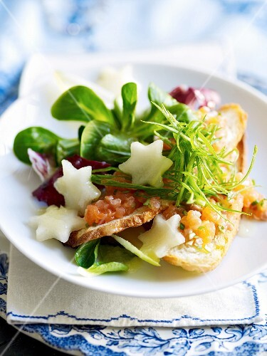 Salmon trout tartar on a bed of lettuce with pear stars