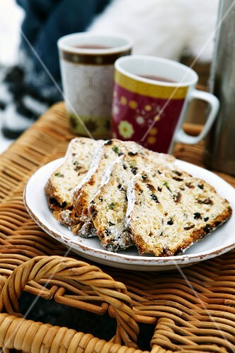A plate of stollen cake and cups of hot drinks on top of a picnic basket in the open air
