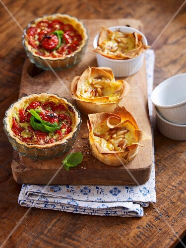 Tomato tartlets and cheesecake with pine nuts on a wooden board