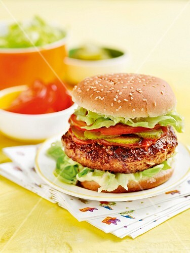 A homemade hamburger with tomatoes, lettuce and cucumber