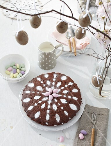 Chocolate cake decorated with icing on a table laid for Easter