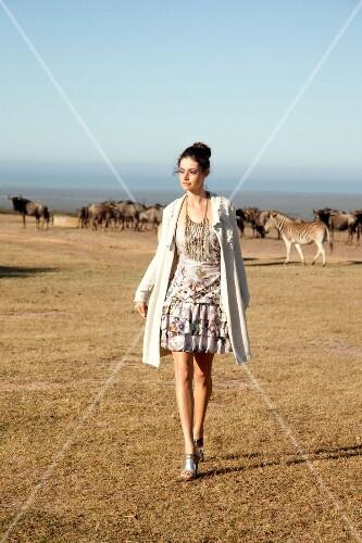 Woman wearing long dress walking in front of animals, Looking away