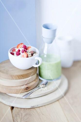 Muesli with honey berries and yogurt and a bottles of cucumber shake