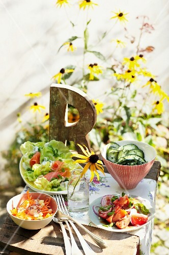 Four different side salads on a table outside