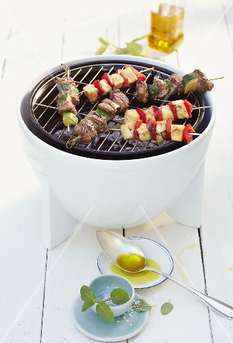 Lamb skewers and halloumi skewers on a barbecue