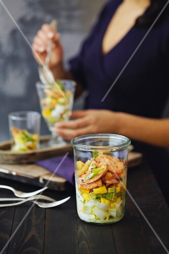 A layered salad with endives, chicken breasts, mango and avocado