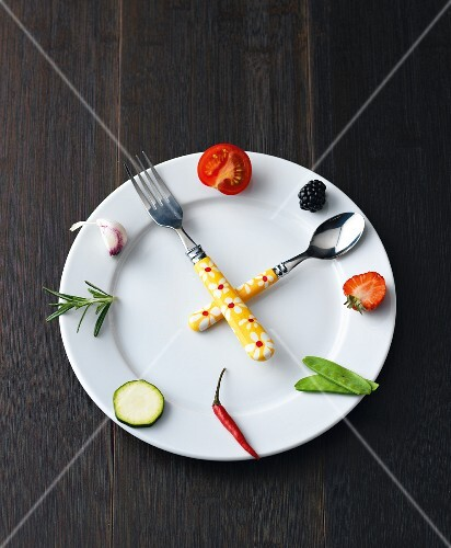 Express cooking: a clock made from a plate, fruit, vegetables and cutlery
