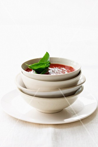 Tomato soup in a bowl against a white background
