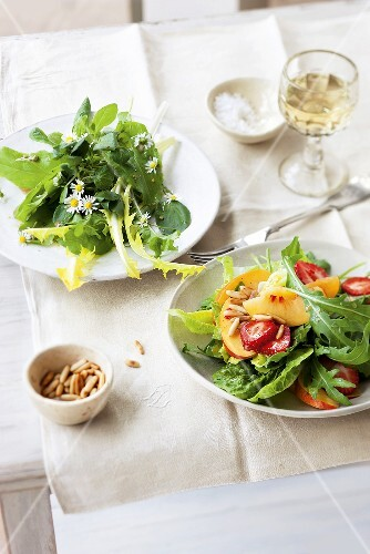 Two summer salads: wild herb salad, and a mixed leaf salad with fruits