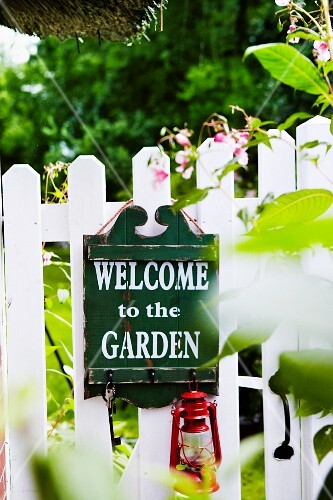 Wooden sign with welcome message on garden fence