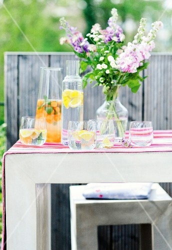 Fruit flavoured water and a bunch of flowers on a table outside