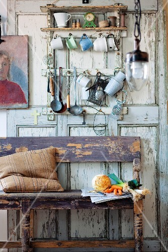 Vegetables for soup on kitchen bench below utensils on wall in rustic kitchen