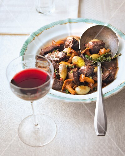 Game goulash with chanterelle mushrooms and a glass of red wine
