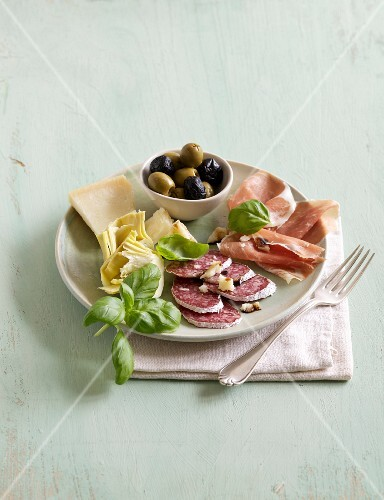 An appetiser platter of salami, ham, cheese, olives and artichokes