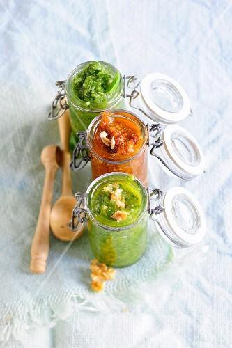 Basil pesto, tomato pesto and walnut pesto in flip-top jars