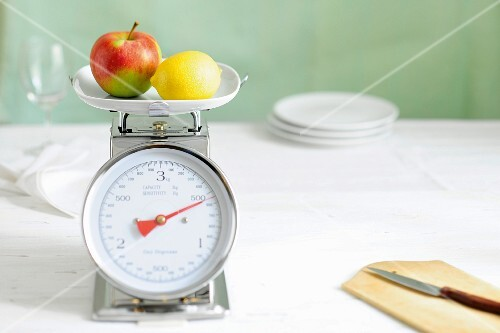 An apple and a lemon on a pair of scales
