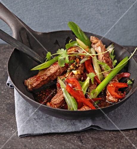A stir-fried rib eye steak with pepper, spring onions and coriander