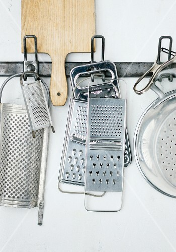 Various graters and vegetable slicers hanging on a wall