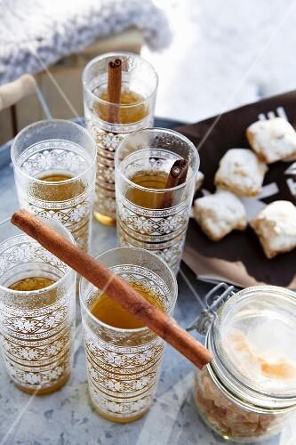 Tea with cinnamon sticks in oriental glasses outside