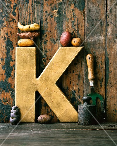 An arrangement featuring a golden letter K and various types of potatoes